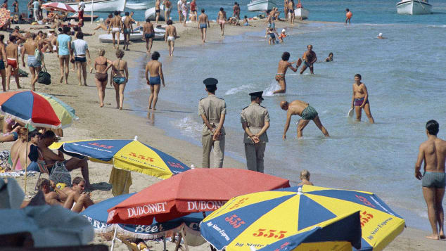 Famagusta beach filled with swimmers, sailors and police who walk the beach with hands behind them for security reasons, in 1970, Kyrenia, Cyprus.
