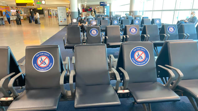 Seats outside the gates instruct travelers to abide by social distancing protocols.