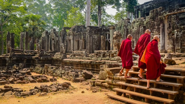 Buddhist monks enter the Bayon Temple at Angkor Wat in Cambodia.