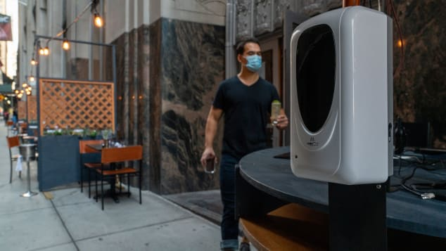 A hand sanitizer dispenser is stationed in the outside dining area of Crown Shy restaurant in New York.