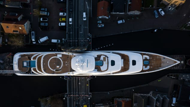 The 94-meter vessel is maneuvered across a bridge in Woubrugge during the tricky journey.