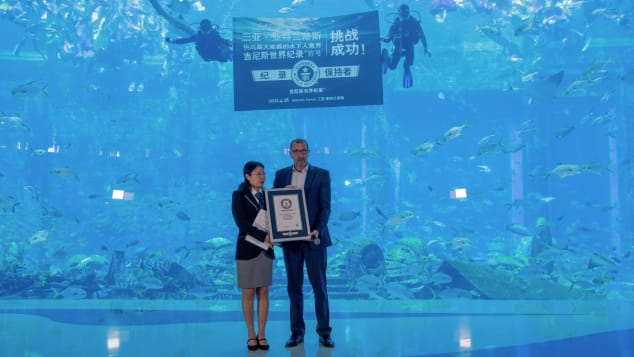 Heiko Schreiner, managing director of Atlantis Sanya, receives a certificate from Wu Xiaohong of Guinness World Records following the April 28 mermaid event.