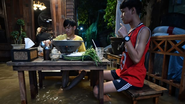People enjoy dinner at the Chaopraya Antique Cafe, as flood water from the Chao Phraya river surges into the restaurant.
