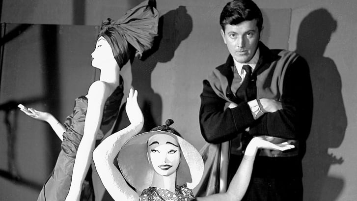 In this 1952 file photo, French fashion designer Hubert de Givenchy poses with mannequins in his shop in Paris.