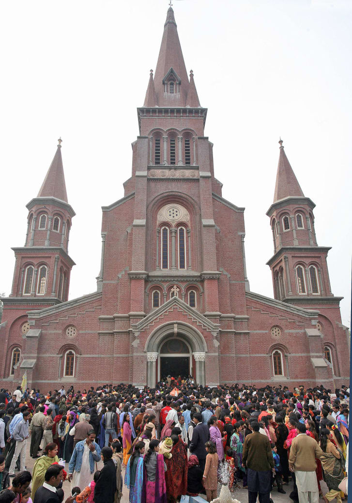 Pakistani Christians gather after attending a Christmas mass outside the Sacred Heart Cathedral Church in Lahore.