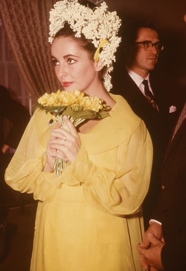 Elizabeth Taylor wore a striking yellow dress and floral headdress for her 1964 wedding to Richard Burton.