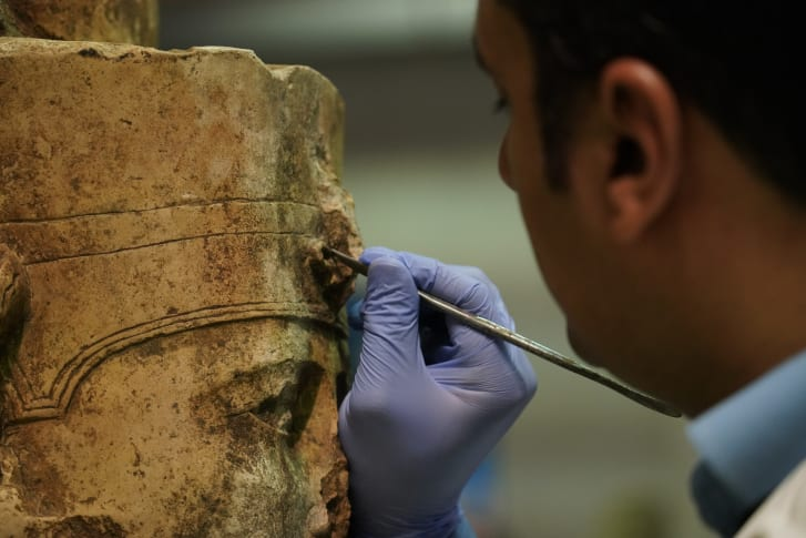 A conservator works on a statue of Amun-Ra in the heavy stone room at the Grand Egyptian Museum conservation center.