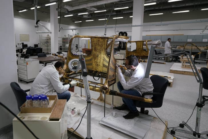 Conservators work on the restoration of a chariot from Tutankhamun's tomb at the Wood Laboratory in the Grand Egyptian Museum's conservation center.