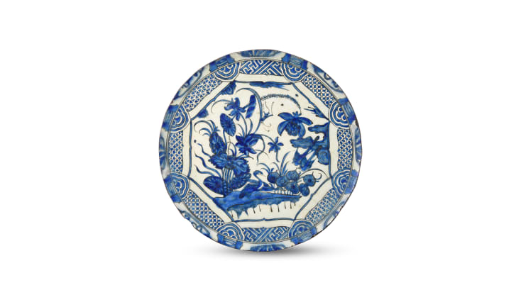 A blue and white dish produced in 17th century Persia depicts diving waterfowl amid plants and flowers. It is an example of