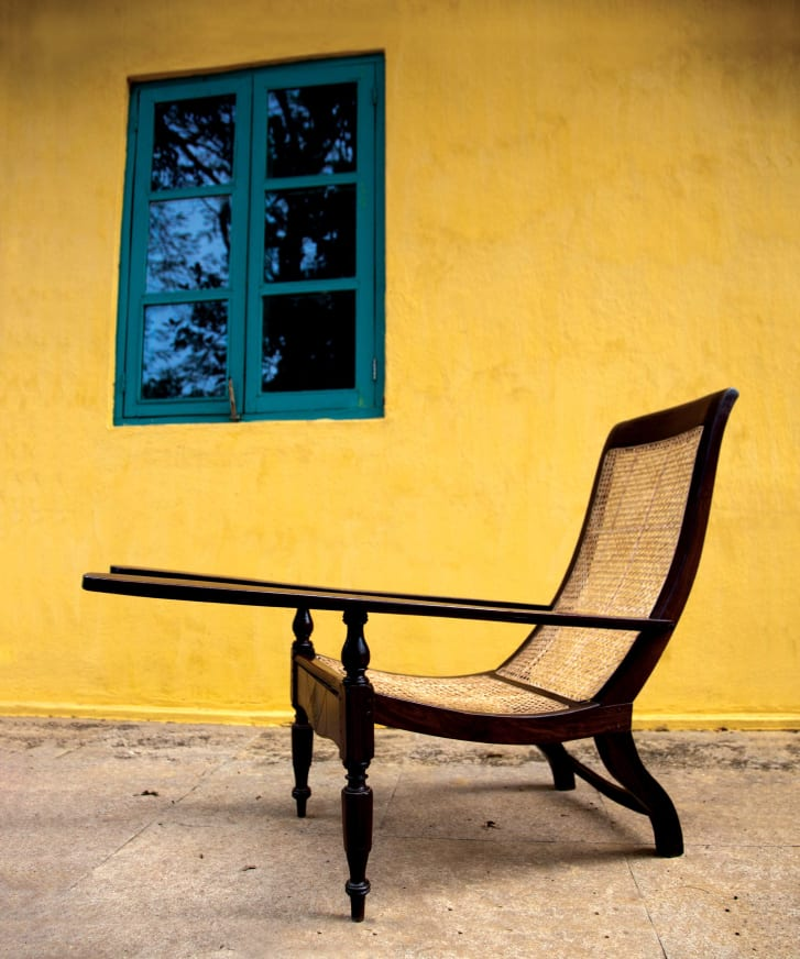 The planter's chair is thought to have been imported to India from Sri Lanka by the British. It has become a staple of the county, with its cane weaving much more suitable to the climate than a sofa.