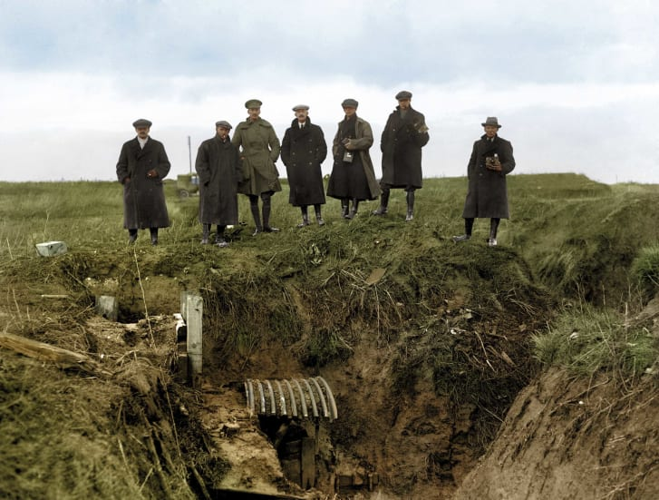 Journalists look down into a First World War trench.