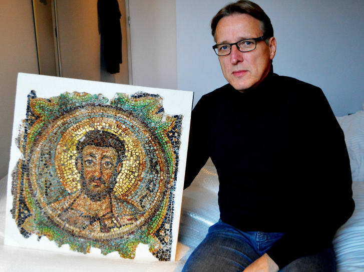 Dutch art detective Arthur Brand poses with the missing mosaic of St. Mark, a rare piece of stolen Byzantine art from Cyprus.