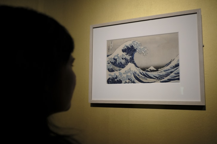 "A visitor looks at Katsushika Hokusai's famous print, ""The Great Wave off Kanagawa,"" at the Ara Pacis Museum in Rome."