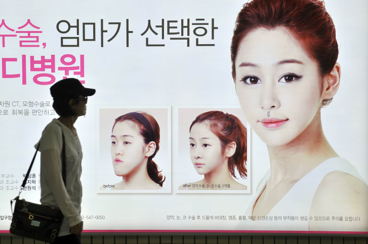 A billboard advertises cosmetic jaw surgery at a subway station in Seoul.