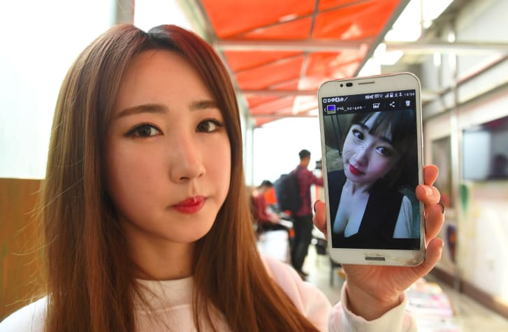 Lee So-Young, a member of K-pop group SixBomb, shows a photo of herself before her plastic surgery at a beauty parlour in Seoul.