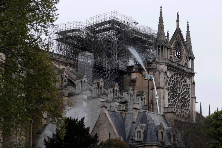 Firefighters spray water as they work to extinguish a fire at Notre Dame Cathedral in Paris early on April 16, 2019.