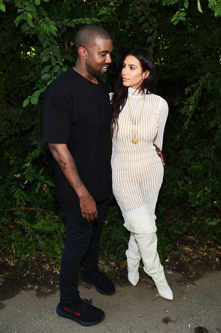 Kanye West, with wife Kim Kardashian, wearing a pair of Yeezy sneakers in 2016.
