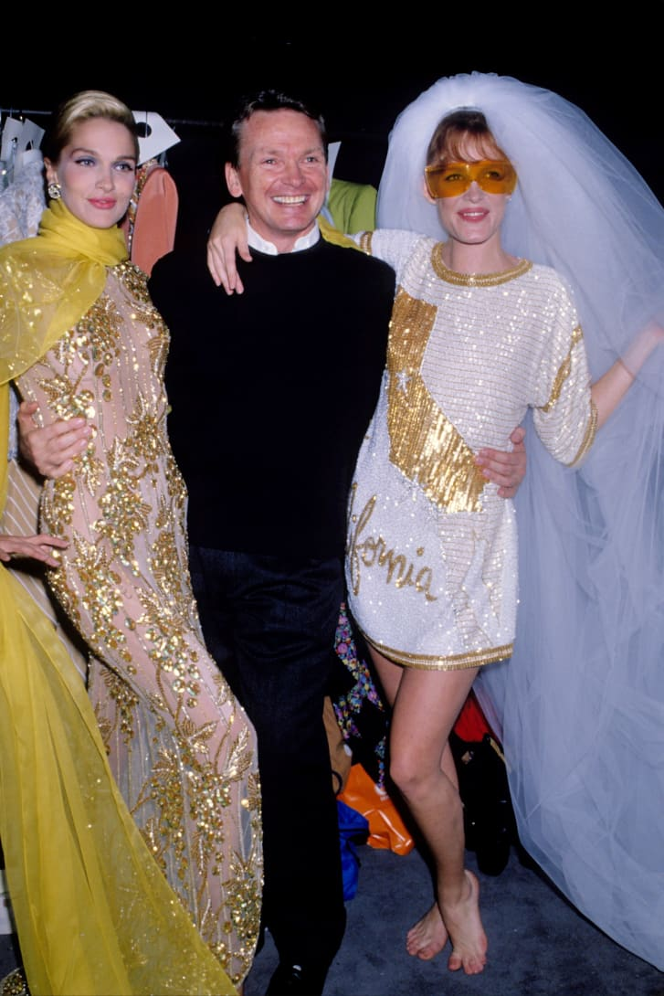 Bob Mackie poses with models during New York Fashion Week in the late 1980s.