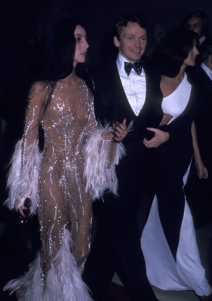 Cher, wearing a Bob Mackie design, accompanies the actual Bob Mackie to the 1974 Met Gala.