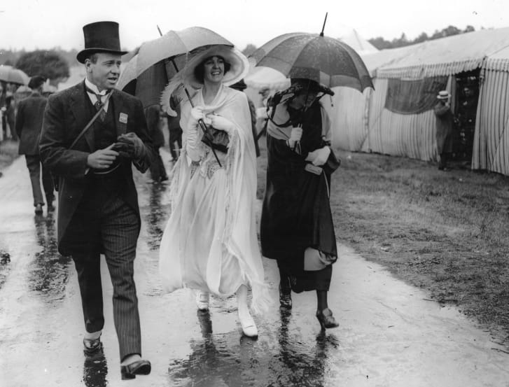 While their male companion looks traditionally formal, the ladies embraced more carefree silhouettes at the 1922 Royal Ascot -- despite the rain.