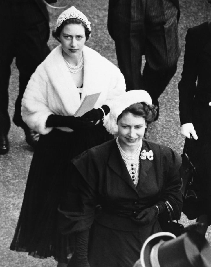 Queen Elizabeth II, dressed in black with a white hat, followed by Princess Margaret at the the second day of Royal Ascot in 1952.