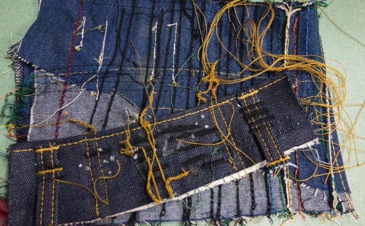 Pieces of denim reveal practice stitches.