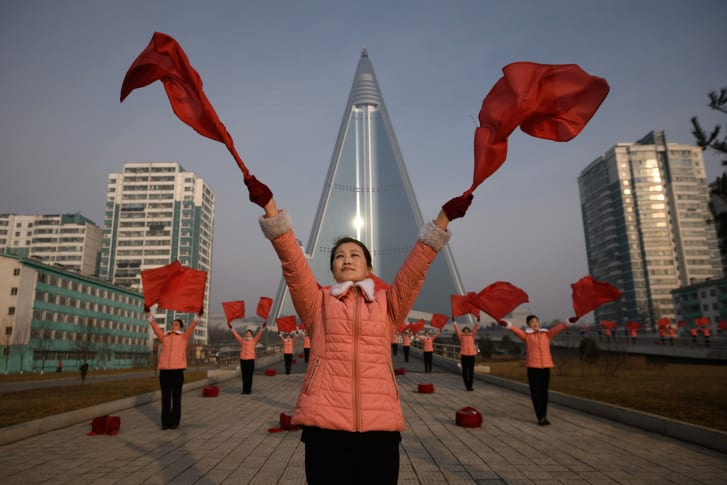 Members of a Socialist Women's Union propaganda troupe perform a dance in front of the Ryugyong hotel in 2019.
