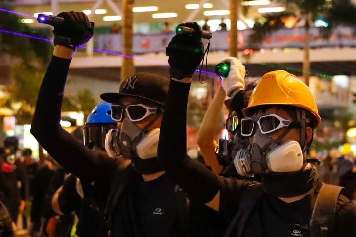 Protesters point laser beams at policemen during a protest in Hong Kong, on August 11, 2019.