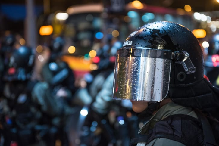 A policeman wears metallic gray material in his helmet as he stands on guard in the rain during a peaceful demonstration in Hong Kong.