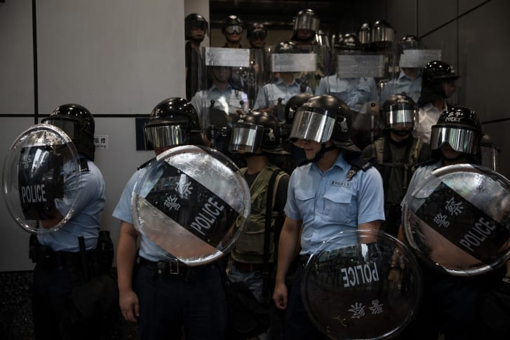 Police stand guard outside Mong Kok police station as pro-democracy protesters gather on August 17, 2019 in Hong Kong.