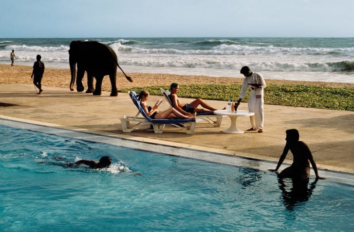 Tourists lounge poolside as an elephant passes in Bentota, Sri Lanka. 1995.