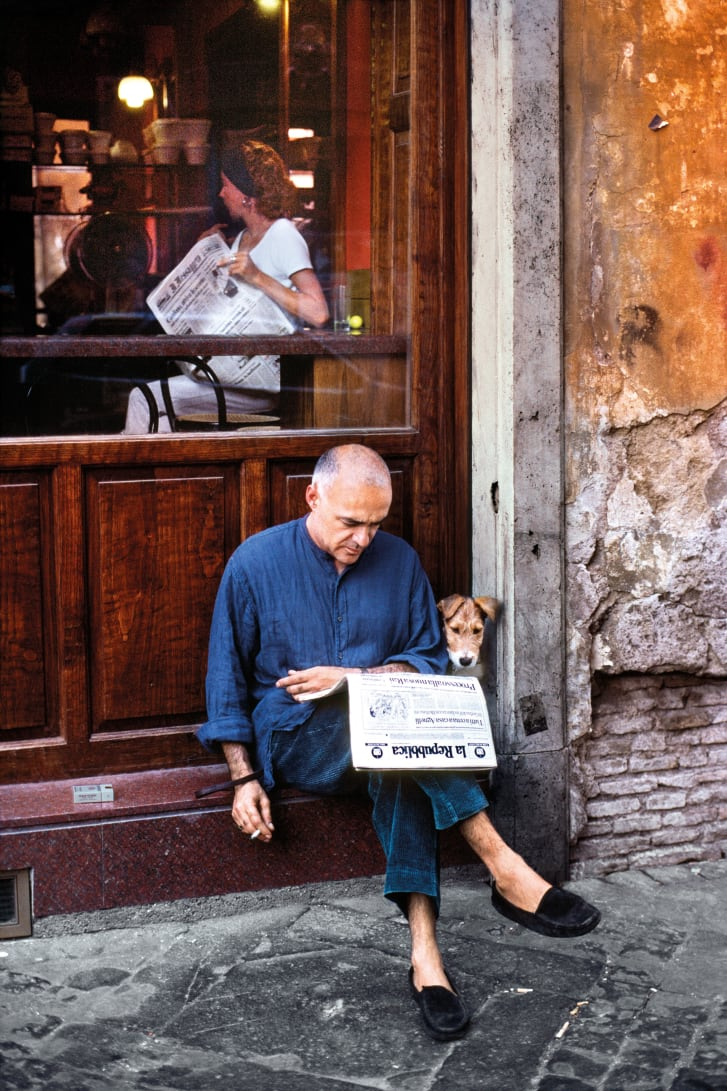 A man reads the newspaper with his dog outside a restaurant in Rome, Italy, 1994.