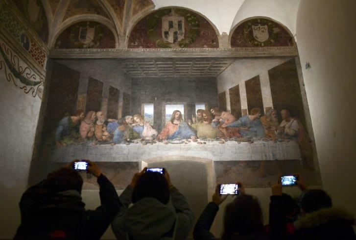 """Visitors take photos of """"The Last Supper"""" (""""Il Cenacolo or L'Ultima Cena"""") at the Convent of Santa Maria delle Grazie in Milan, Italy."""
