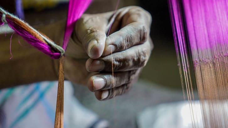 Master silk weaver Ranzan Ali ties together each individual thread to the handloom from his workshop in Varanasi.