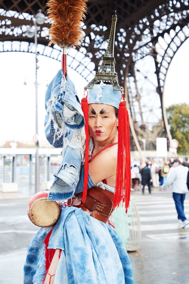 An outfit made of recycled denim, a miniature Eiffel Tower and long, red Chinese tassels.