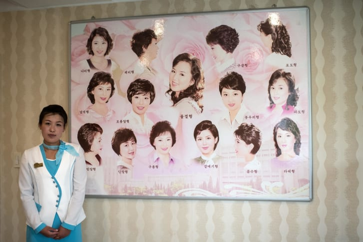 A staff poses next to a board displaying approved hairstyles at a women's salon in the Munsu Water Park complex in Pyongyang, North Korea in 2018.