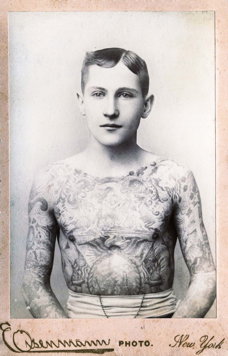 Cabinet photograph, by Eisenmann, of a young man with his entire chest and arms tattooed, New York, circa 1890.