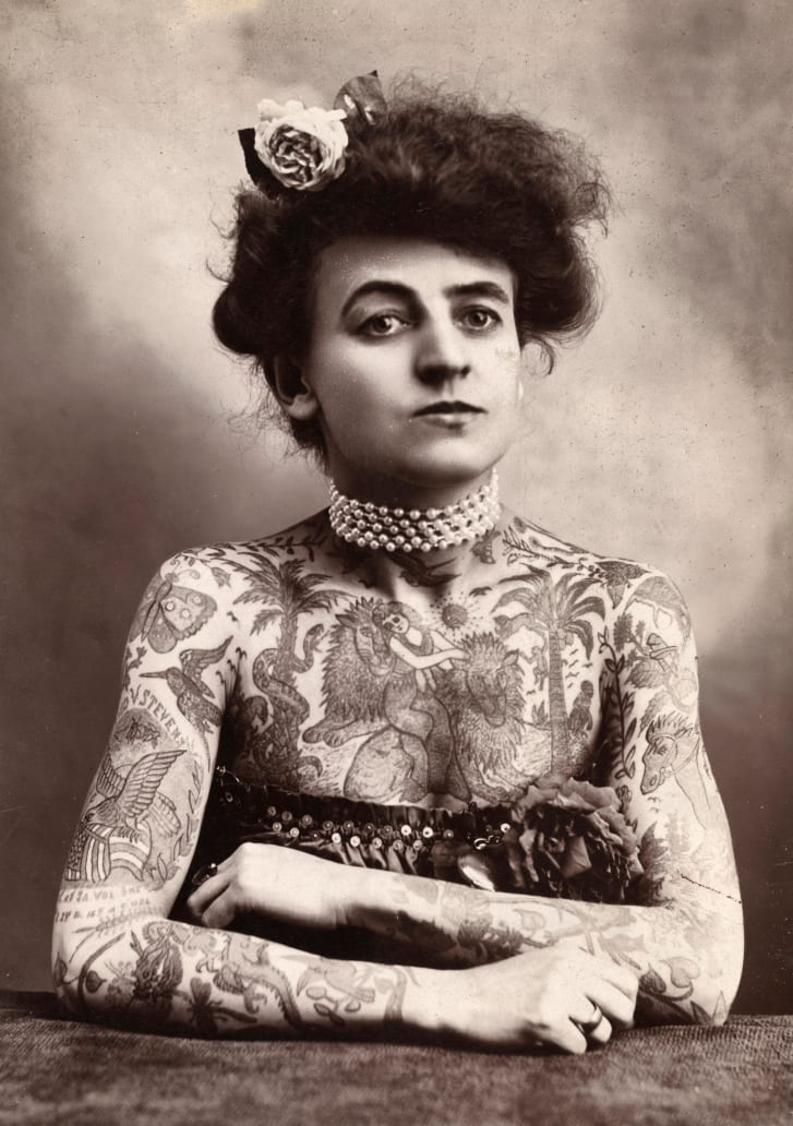 Portrait of a woman with tatooes or body paint covering her arms and chest.
