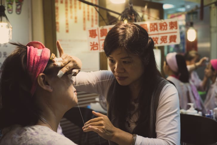 Threading -- which removes facial hair -- has long been a traditional beauty procedure, as seen in this picture at a Taipei night market. A thin thread is doubled, then twisted and rolled over areas of unwanted hair, plucking the hair at the follicle level.
