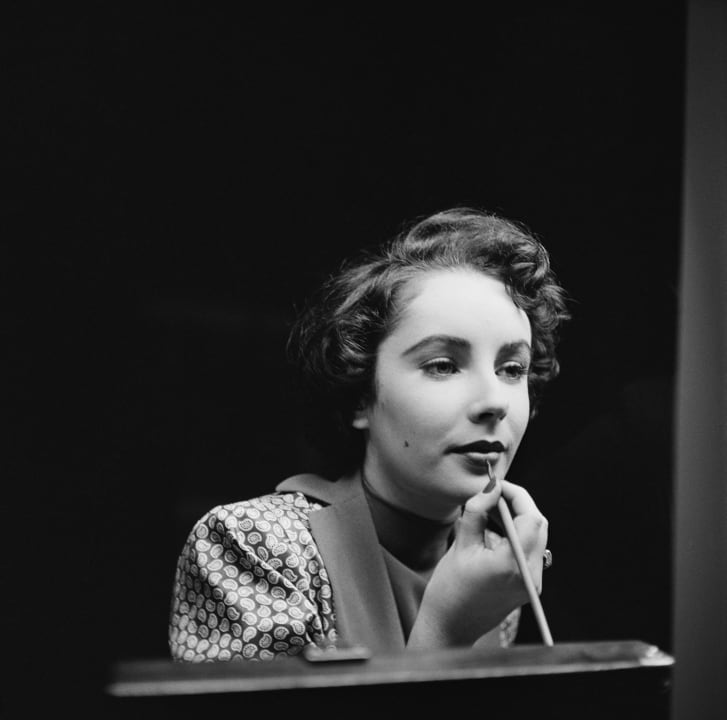 Actress Elizabeth Taylor touches up her lipstick (1948)