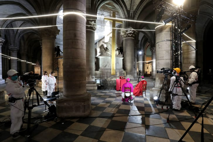Auxiliary Bishop of Paris Denis Jachiet, center, and Archbishop of Paris Michel Aupetit, left, attend a meditation ceremony to celebrate Good Friday in a secured part of Notre Dame.