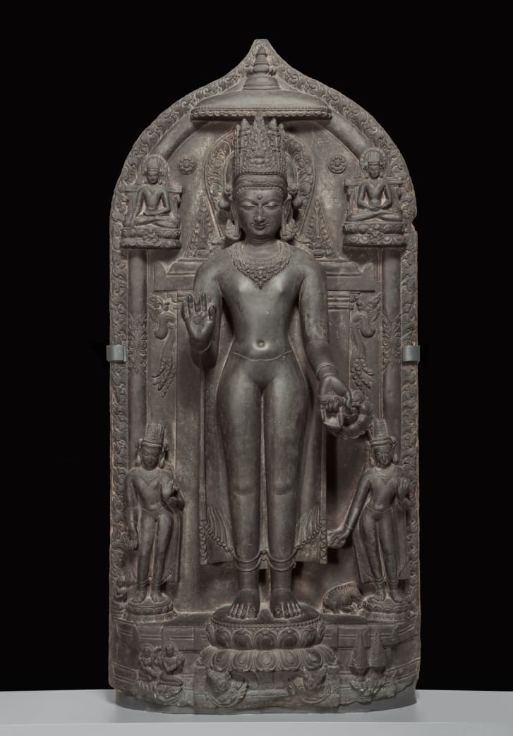 """A basalt statue: """"Standing crowned Buddha with four scenes of his life,"""" approx. 1050--1100. southern Magadha region, Bihar state, India. Part of the Brundage Collection at the Asian Art Museum, San Francisco."""