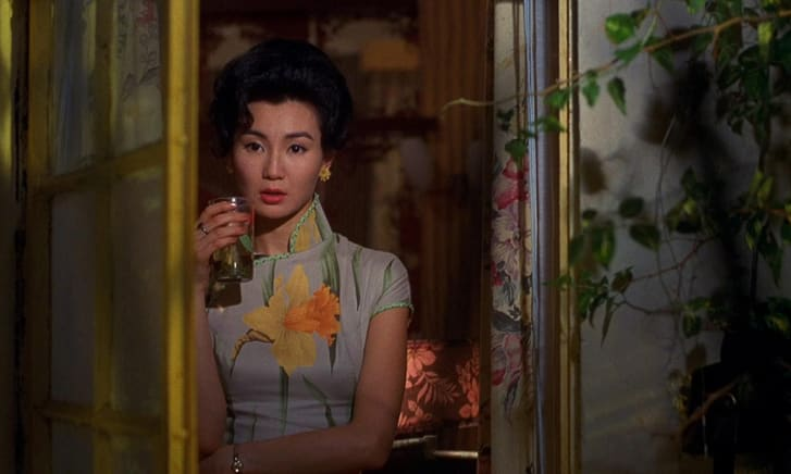 The costumes often mirror the surroundings, such as this scene where Mrs. Chan's daffodil print dress stands out among other floral motifs.