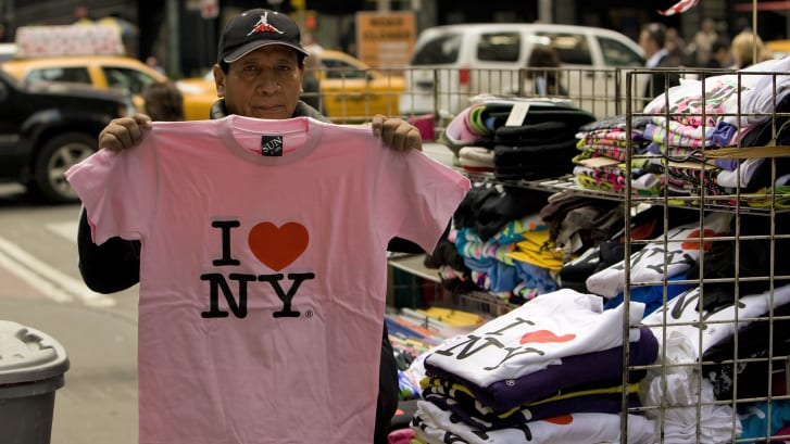 """A street vendor holds up an """"I ♥ NY"""" t-shirt in 2009."""