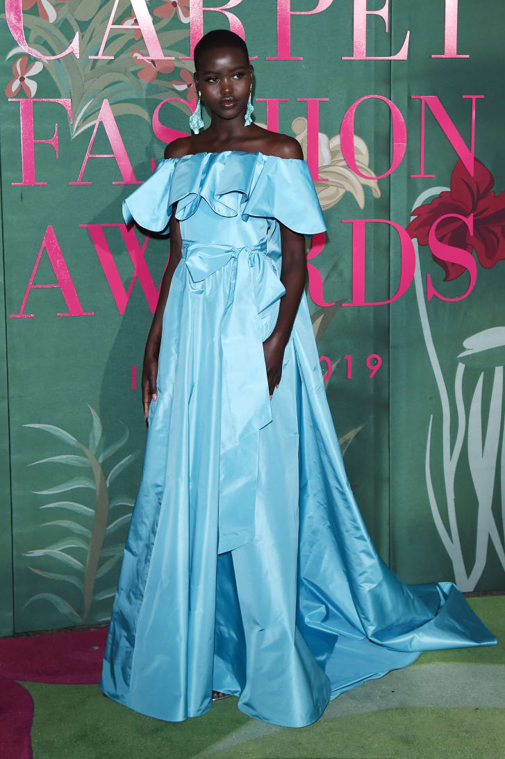 """Model Adut Akech attends the Green Carpet Fashion Awards in 2019. Her turquoise Valentino """"eco-couture"""" gown was made of reclaimed materials and organic silk."""