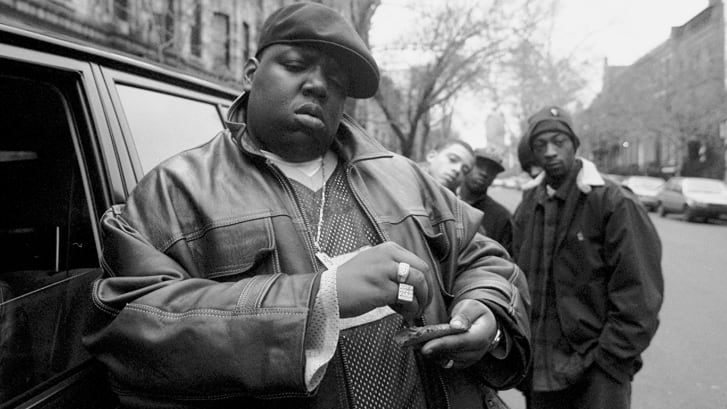 Terkenal BESAR alias Biggie Smalls alias Chris Wallace melinting cerutu di luar rumah ibunya di Brooklyn.