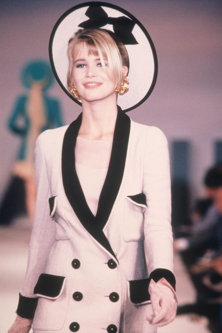 Claudia Schiffer, wearing big gold earrings, walks the runway during the Chanel Haute Couture show as part of Paris Fashion Week in January 1990.