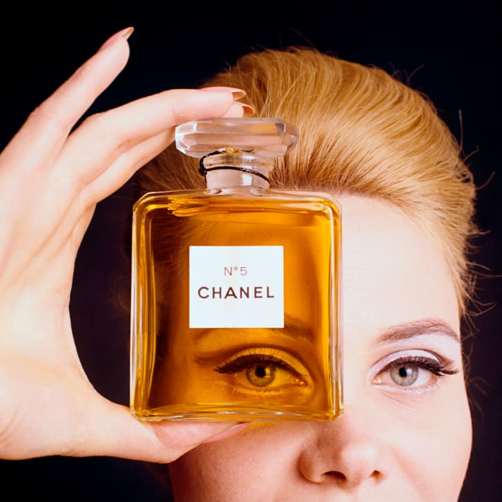 Close up of model holding a bottle of Chanel No. 5 perfume.