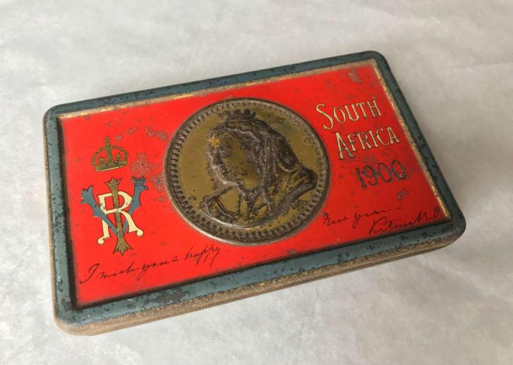 A red rectangular chocolate tin with Queen Victoria's face on the top.