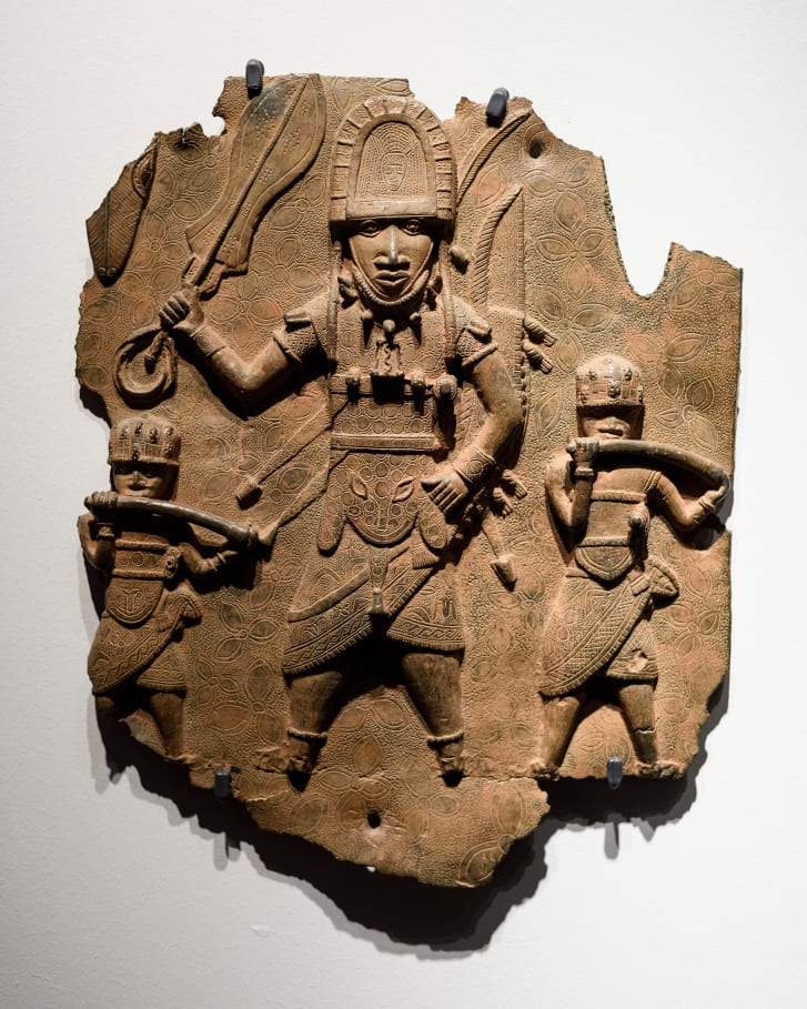 A Benin Bronze, pictured in Berlin, depicts a high-ranking dignitary with sword and rectangular bell accompanied by two hornblowers, brass plaque.